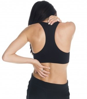 Woman in sports bra, back turned to viewer, holding her neck and lower back to signify pain.